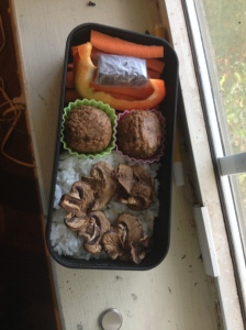 This bento features a peanut chew, carrot and bell pepper sticks, along with mushrooms and rice.