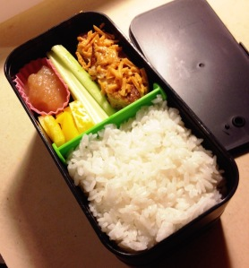 This bento contains Gardein Chick'n Nuggets topped with Daiya Cheddar, celery sticks, applesauce, yellow peppers and white sticky rice.